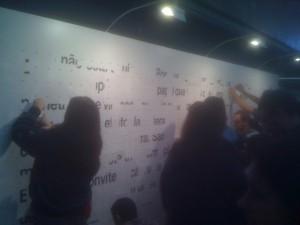 Pessoas montando mosaico no TEDxUSP com adesivos oferecidos na entrada